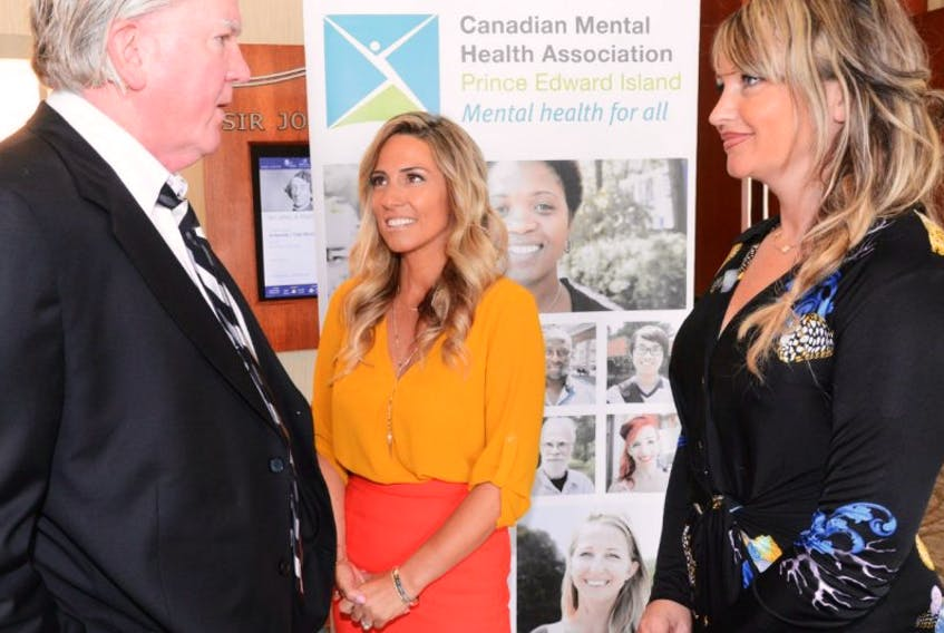 Brian Burke chats with Kate Flanagan, organizer, and Nicole MacLeod, Canadian Mental Health Association, before a lunch fundraiser for the Canadian Mental Health Association held at the Delta Hotel on Aug. 31, 2015.