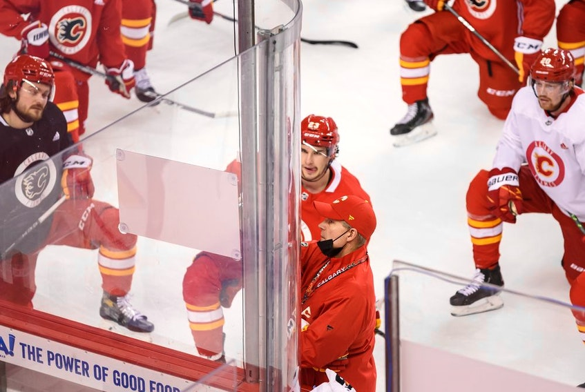 Calgary Flames players listen to head coach Geoff Ward during team practice at the Saddledome earlier this season.