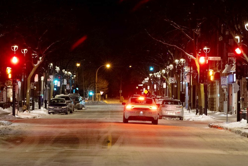 Montreal police patrol Wellington St. during the Quebec-wide curfew.
