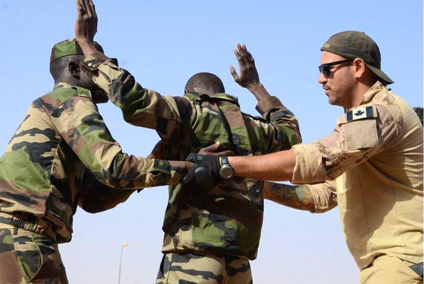 A Canadian Special Operations Regiment instructor teaches soldiers from the Niger Army how to properly search a detainee in Agadez, Niger, Feb. 24, 2014 during that year's Flintlock exercise.