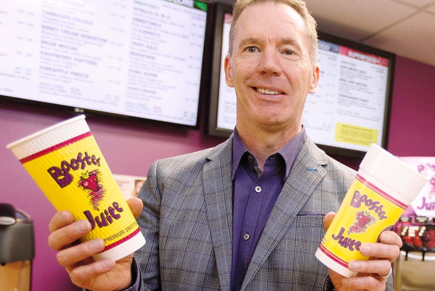 Booster Juice co-founder, president and CEO Dale Wishewan poses for a photo with the company's new cup (left) and old cup in the Booster Juice Test Kitchen at AW Holdings Corp.'s head office in Edmonton on Friday, January 27, 2017.