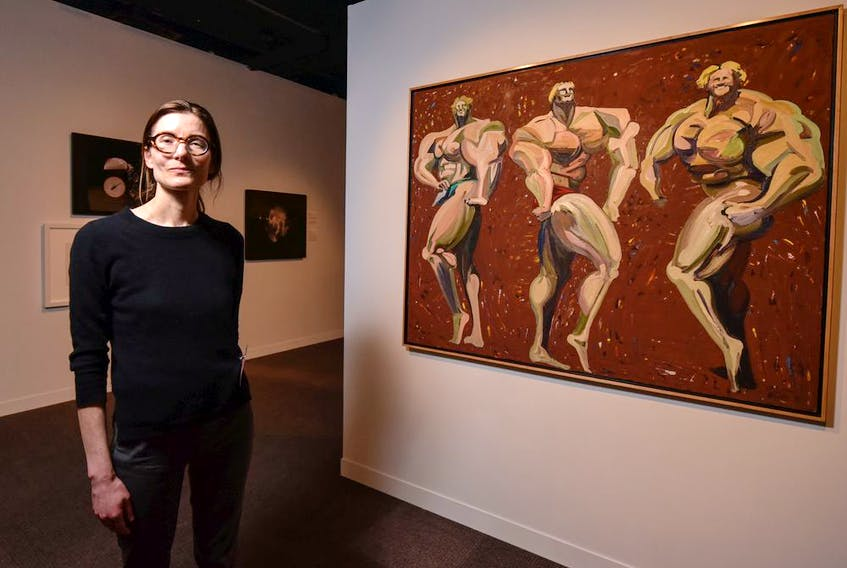 Madeleine Trudeau, co-curator of Metamorphosis: Contemporary Canadian Portraits at the Glenbow Museum, is pictured in front of Harold Town's 1983 oil and lucite portrait Musclemen.