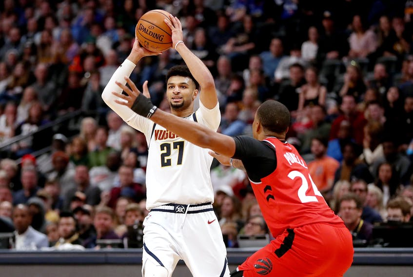Denver Nuggets' Jamal Murray is guarded by Raptors'  Norman Powell during Sunday's game. (GETTY IMAGES)