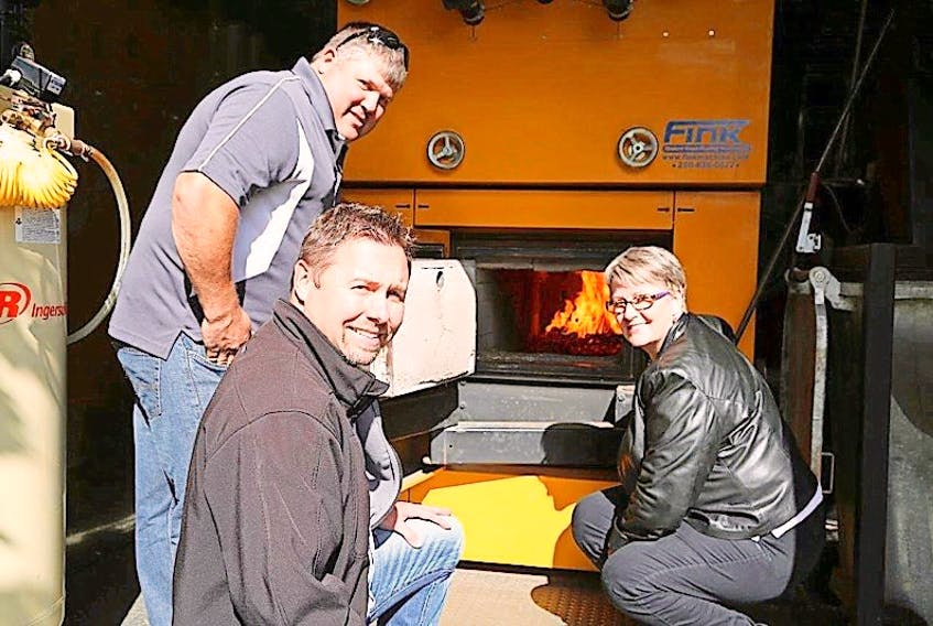 Dick Arsenault, left, and Mathieu LeBlanc of ACFOR Energy examine a burner at the biomass heating facility in use at the Wedgewood Manor in Summerside with Energy Minister Paula Biggar.