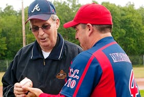 Island baseball legend Vern Handrahan, left, gets the opening-pitch ball back from catcher Craig Cooper of the host Chevies team during the opening ceremonies of the Canadian Oldtimers Baseball Championships at Memorial Field in Charlottetown Thursday, Aug. 2.