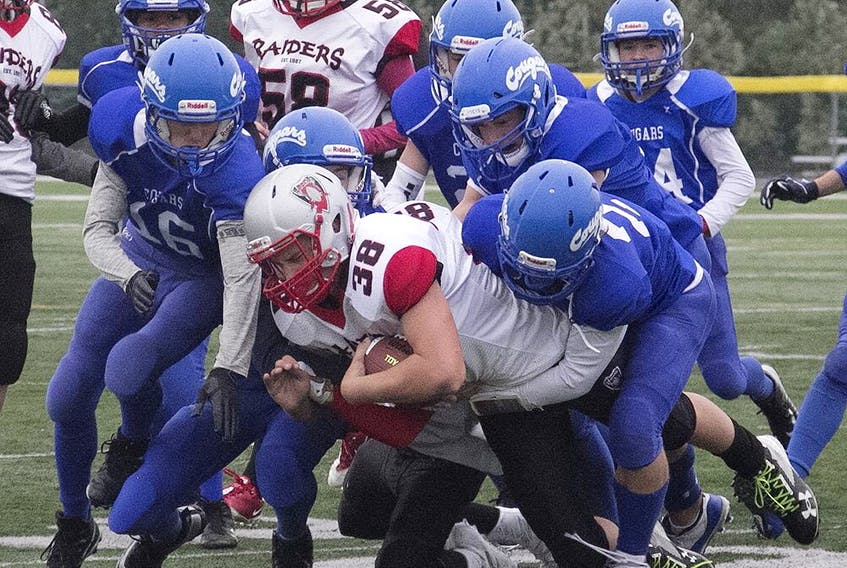 The Spruce Grove Cougars gang tackle a West Edmonton Raiders ball carrier in Capital District Minor Football Association play in September 2019. The association has announced the cancellation of the 2020 Spring season due to COVID-19 measures.