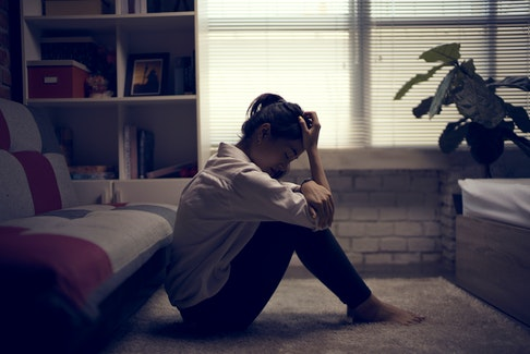 Stock photo of a woman, sad, sitting on the ground in her home, for an article on domestic violence.