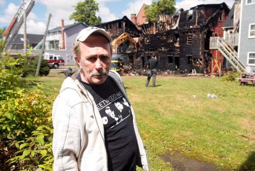 Glenn Ford stands in the yard of a neighbour as he watches fire investigators go about their work in the ruins of what was once his home and the home of his mother.