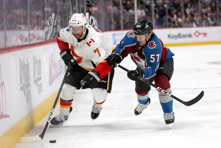 T.J. Brodie of the Calgary Flames fights on the boards with Gabriel Bourque of the Colorado Avalanche in the third period during Game 3 of the Western Conference First Round during the 2019 NHL Stanley Cup Playoffs at the Pepsi Center in Denver on April 15.