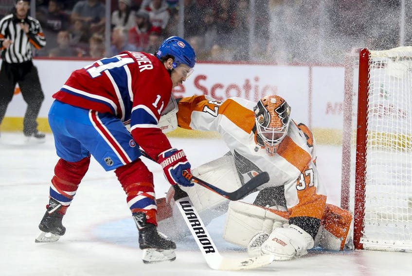 Canadiens' Nick Suzuki protects the puck from Flyers' Travis Sanheim  during game at the Bell Centre in November.