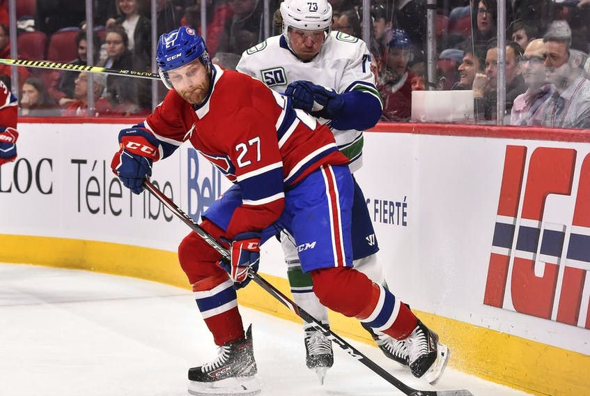 Canadiens' Karl Alzner  keeps the puck from Canucks' Tyler Toffoli during the first period Tuesday night at the Bell Centre.