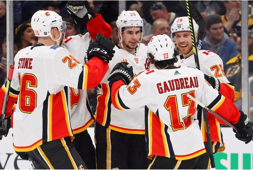 Flames centre Sean Monahan celebrates with Elias Lindholm, Johnny Gaudreau and Michael Stone after scoring a goal against the Boston Bruins during the second period at TD Garden on Tuesday night in Boston.