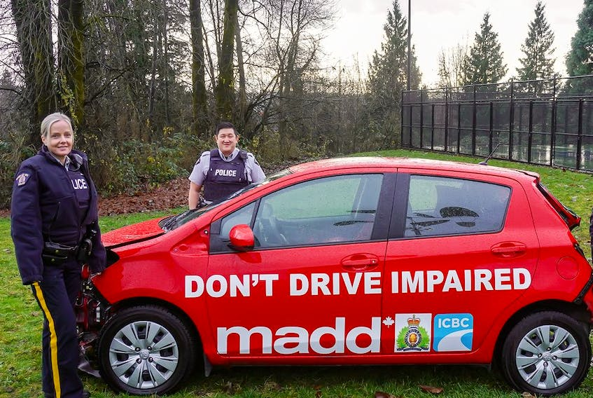 RCMP officers pose with a Mothers Against Drunk Driving (MADD) vehicle.