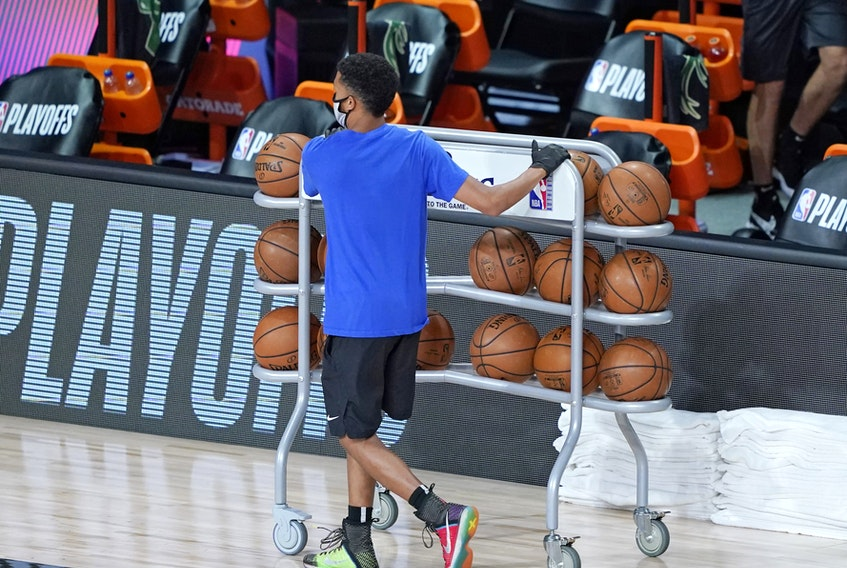 A worker wheels away the warmup basketballs from the Milwaukee Bucks bench after the scheduled start of their game on Wednesday was postponed following the teams boycott.