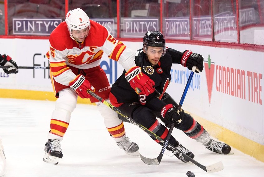 Artem Zub (right) of the Ottawa Senators battles for a loose puck against Mark Giordano of the Calgary Flames at Canadian Tire Centre on March 1, 2021 in Ottawa.