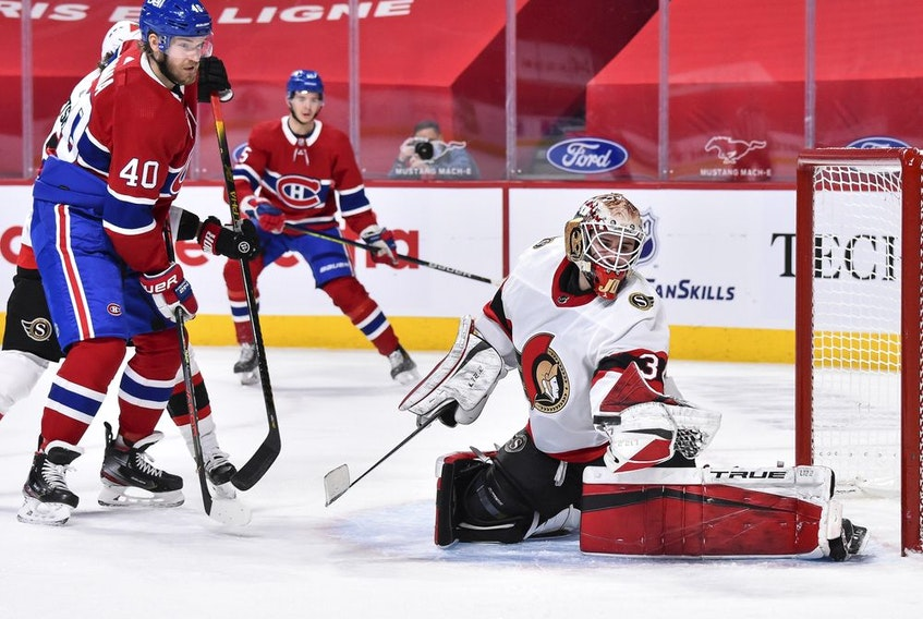 The Ottawa Senators' Joey Daccord redirects the puck with his glove near Joel Armia of the Montreal Canadiens during the second period at the Bell Centre on March 2, 2021.