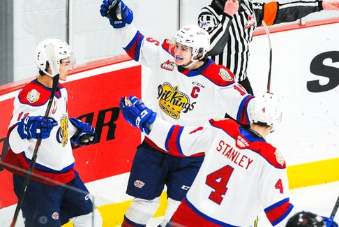 Dylan Guenther (11) of the Edmonton Oil Kings celebrates with teammates Scott Atkinson (15) and Ross Stanley (4) after scoring against the Calgary Hitmen at 7 Chiefs Sportsplex on March 27, 2021, on Tsuut'ina Nation.