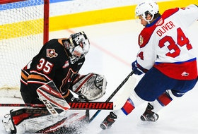 Brayden Peters (35) of the Calgary Hitmen stops a shot from Kaid Oliver (34) of the Edmonton Oil Kings at Seven Chiefs Sportsplex on March 27, 2021, in Calgary.