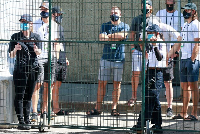 The Vancouver Canucks navigate protective fencing on their way to practice at Rogers Place on July 28 in Edmonton.