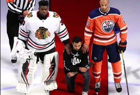 Matt Dumba of the wild is flanked by Blackhawks goalie Malcolm Subban and Oilers' Darnell Nurse during the U.S. anthem prior to a playoff game at Edmonton in August.