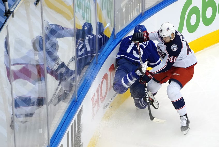 Alexander Kerfoot of the Maple Leafs is hit by Dean Kukan of the Columbus Blue Jackets in Game 1 last night in Toronto.