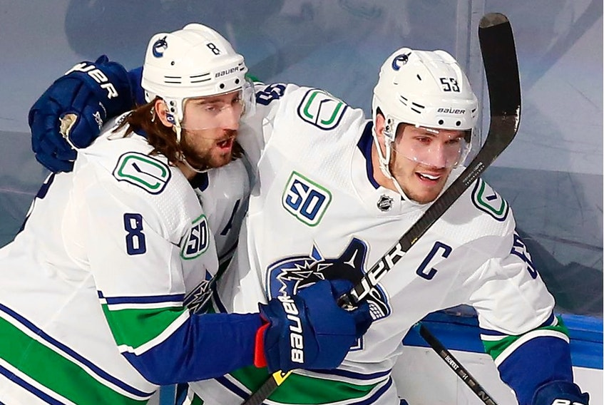 Captain Bo Horvat of the Vancouver Canucks celebrates his shorthanded goal on Friday in Edmonton with Chris Tanev. Horvat also scored in overtime as Vancouver grabbed a 2-0 series lead against the St. Louis Blues.