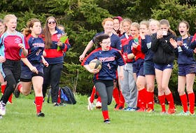With her teammates proudly cheering her on, Sierra Holmes, a Grade 9 student at Tantramar Regional High School with Down Syndrome, runs down the field to score her first try during last Thursday's final home game of the season for the TRHS women's rugby Titans. SCOTT HEMS PHOTO