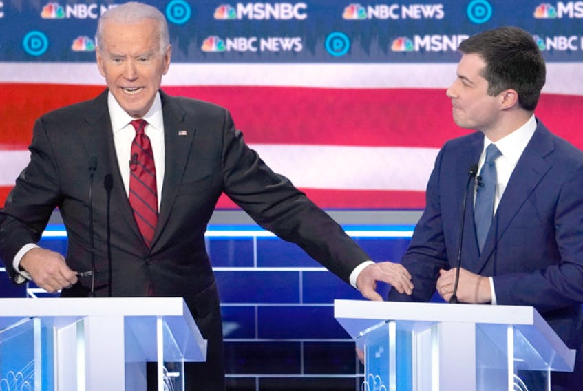 Joe Biden grabs the arm of Pete Buttigieg as he speaks during the ninth Democratic U.S. presidential candidates debate in Las Vegas, Nevada, U.S., February 19, 2020.