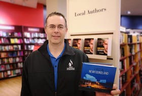St. John's based photographer, Michael Winsor, with his new book of photography, 'Lost in Newfoundland.' - Andrew Waterman/The Telegram