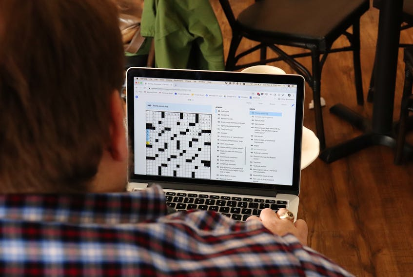 In a Halifax coffee shop, Paul St-Amand concentrates on filling in the New York Times crossword puzzle. Dedicated to his goal of completing 3,653 crosswords before Dec. 29, 2019 in honour of his late father, he works on them whenever he has a spare minute.