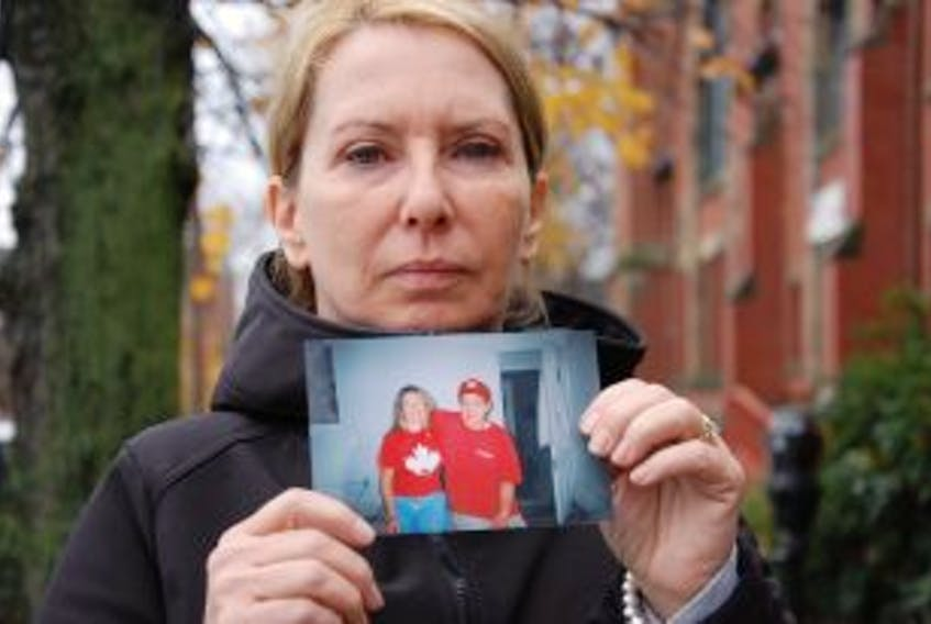 """[""""Dianne Young of Charlottetown holds a photo of her and son Lennon Waterman during a happier period in her son's life.""""]"""