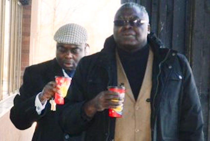 ['Sylvain Aritho Amfoubalel, left, walks to court with friendNoel Ayangma Monday, March 24.']