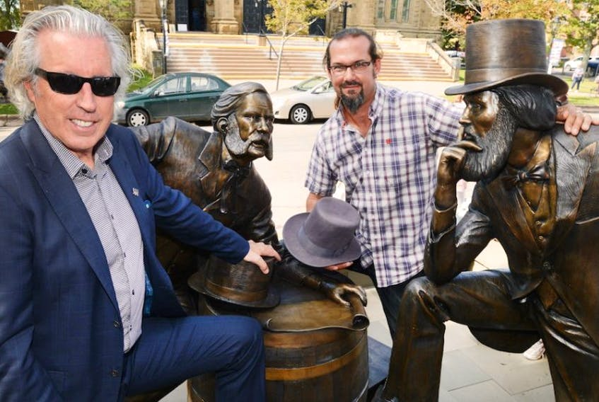 """<p class=""""p1"""">Kevin Murphy, left, and artist Nathan Scott, stand with the newly unveiled bronze statue of two Fathers of Confederation named John Hamilton Gray. The statue, situated on Great George Street was unveiled during a ceremony held Thursday.</p>"""