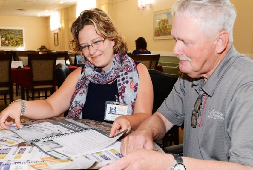 Denise Lockhart, executive director of Family Service P.E.I. and George Noble, chair of the Gulf Shore Community Health Corporation, look over a new financial literacy toolkit for seniors.