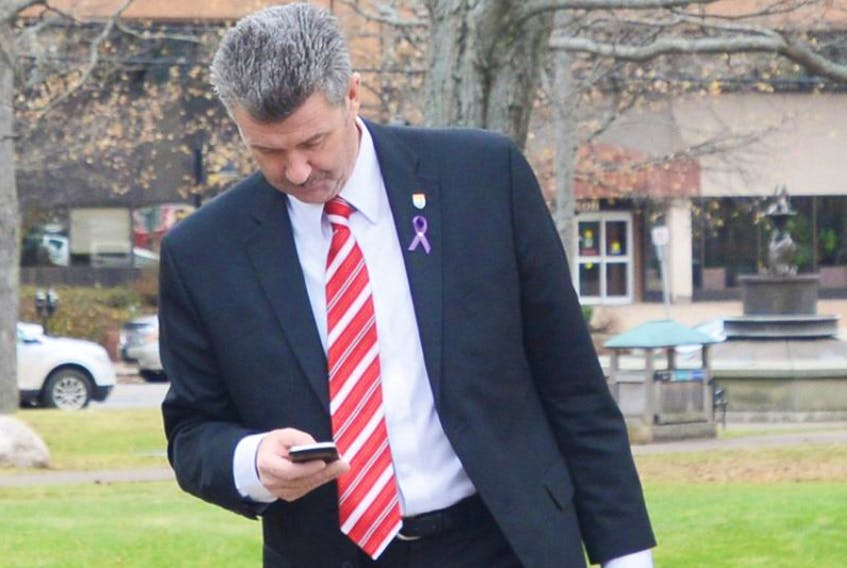 Finance Minister Wes Sheridan checks his phone on the way to the provincial legislature Wednesday afternoon.