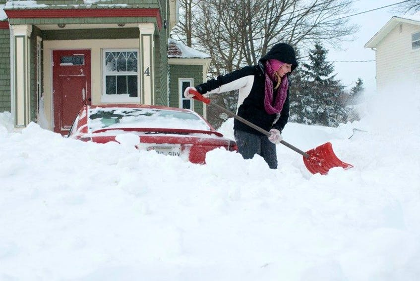 Amy Doucette of Charlottetown shovels her car out from a snowbank after an earlier winter storm.