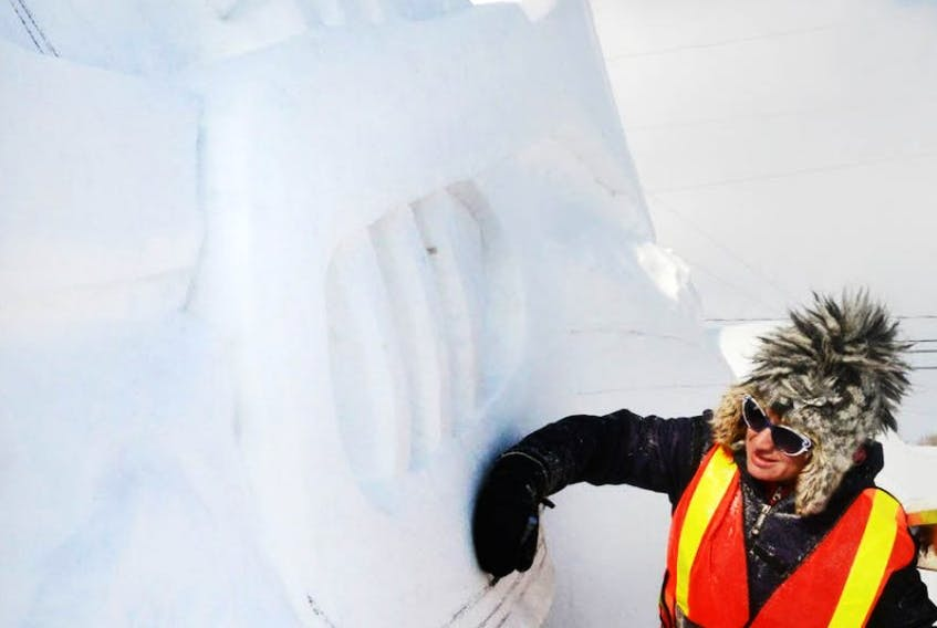 Morgan Rudluff, a snow sculptor, sketches out the outline of a trumpet for the Jack Frost Festival. This year's festival theme is music. The festival will be held this weekend.