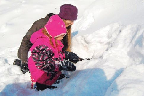Four-year-old Ellen Jadis, who attends Abegweit First Nation Early Years Centre in Scotchfort, digs excitedly with Hanna Hameline, Sierra Club P.E.I. Wild Child co-ordinator, to create a cozy cave home where animals might live.