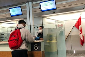 A Canada Border Services Agency (CBSA) officer wears a protective face mask amid coronavirus fears as she checks passports for those arriving at Toronto Pearson International Airport on Sunday, March 15.