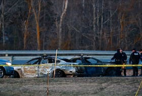 RCMP officers go over a car collision scene involving the fake RCMP car driven by Gabriel Wortman in Shubenacadie, N.S., April 19, 2020.