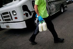 A man delivers milk at Capitol Hill as COVID-19 continues to spread nationwide and public anxiety lingering in grocery stores has created a new surge of interest in home food deliveries, in Washington, U.S., May 18, 2020.