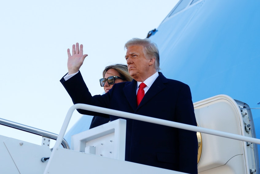 U.S. President Donald Trump, accompanied by first lady Melania Trump, waves as he boards Air Force One at Joint Base Andrews in Maryland on Jan. 20, 2021.