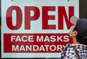 A sign advises that masks are mandatory in a business in Toronto. Canada's economy shrank in July but not as much as expected.