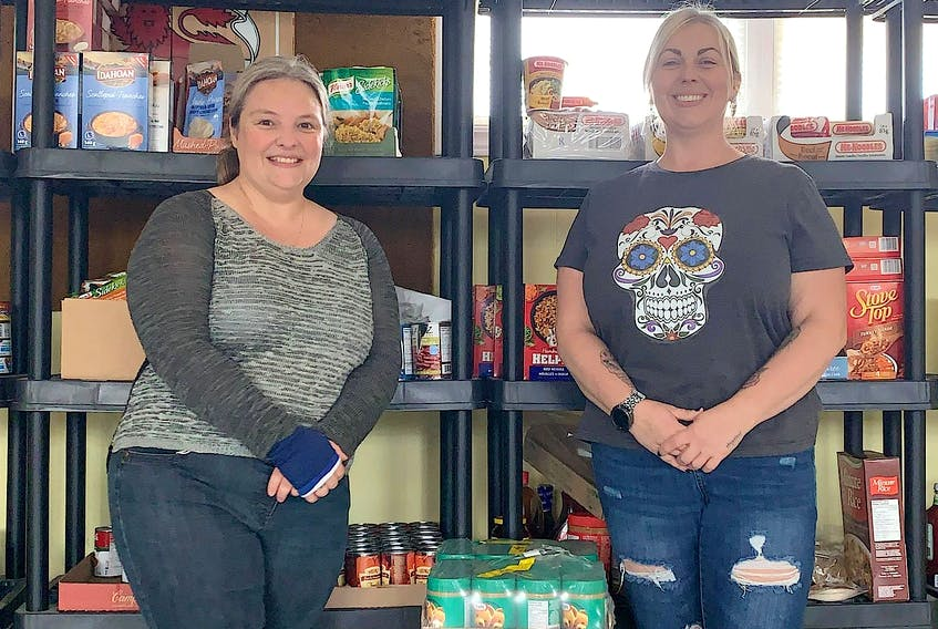 Cindy Holloway, left, and Natasha Howell in front of the food shelf at the Whitney Pier Pensioners Club. Along with another volunteer, Deb Dee, they have been running the Pier Food Pantry for the past year helping 25 households battle food insecurity. CONTRIBUTED • PIER FOOD PANTRY