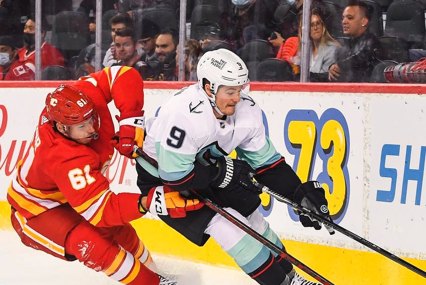 Walker Duehr #61 of the Calgary Flames battles for the puck against Ryan Donato #9 of the Seattle Kraken during an NHL game at Scotiabank Saddledome on September 9, 2021 in Calgary, Alberta, Canada.