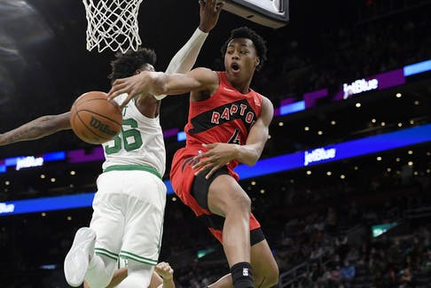 Raptors forward Scottie Barnes (right) passes the ball around Celtics guard Marcus Smart at TD Garden in Boston last night.
