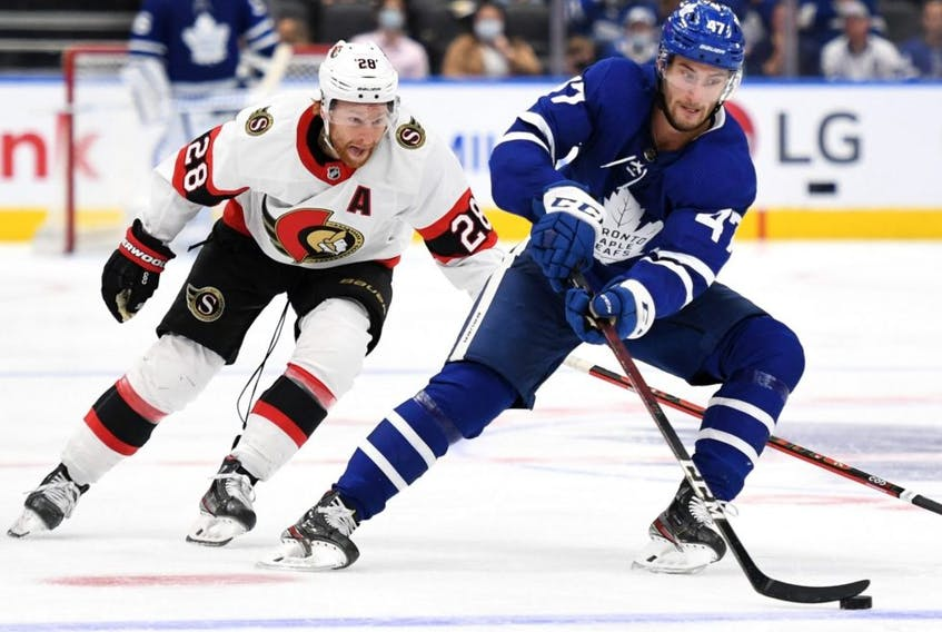 Maple Leafs forward Pierre Engvall (right) carries the puck past Senators forward Connor Brown (left) during preseason NHL action at Scotiabank Arena in Toronto, Saturday, Oct. 9, 2021.