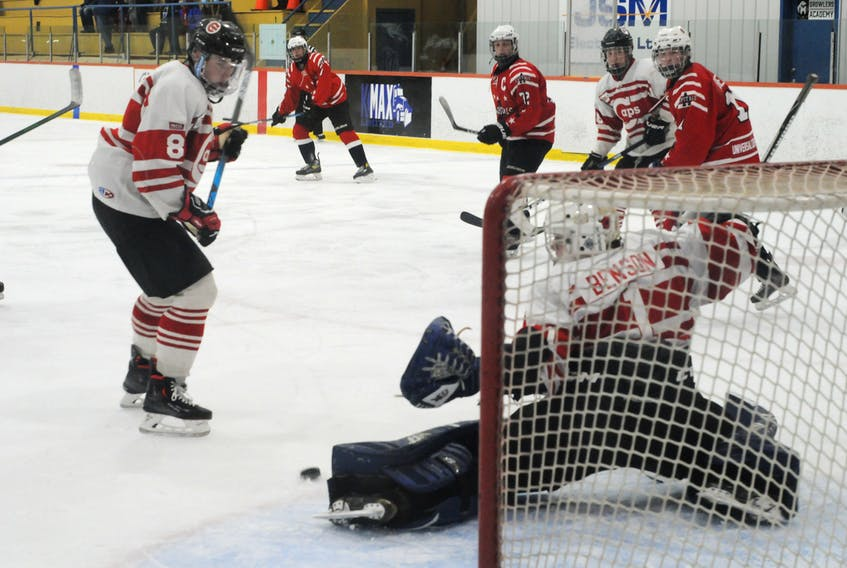 St. John's Caps defenceman George Walsh (8) watches as his team's goalie, Jake Benson, kicks out his left pad to make a save on a shot by Avalon Capitals defenceman Patrick Farrell (rears right) during their St. John's Junior Hockey League game Sunday night at Feildian Gardens. Looking on are Avalon's Evan Gallant (72) and Patrick Beer (11) and Murray Byrne of St. John's. The Caps won 11-5. — Joe Gibbons/The Telegram -Joe Gibbons/The Telegram