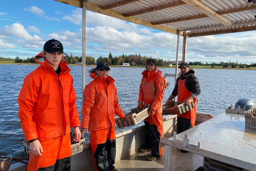 Kordell Ramsay, left, Connie Ramsay, Kaila Richard and Bruce Richard went out to Mill River on Oct. 1 to spread 10 trays of oyster seed in memory of family member Jason Ramsay. Jason, an oyster grower, was killed in a snowmobile accident in February.