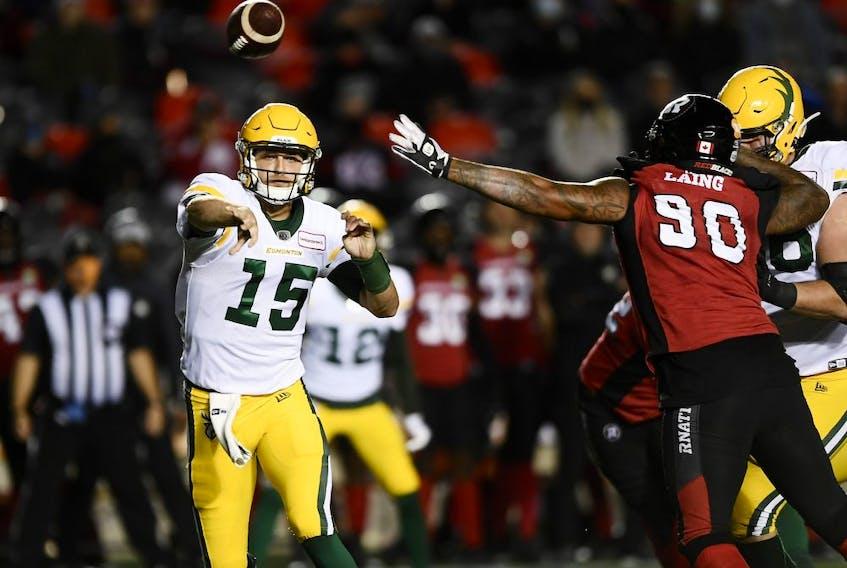 Edmonton Elks quarterback Taylor Cornelius (15) throws the ball past the arm of Ottawa Redblacks defensive lineman Cleyon Laing (90) in Ottawa on Sept. 28, 2021.